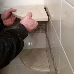 Placing stone corner shower shelf